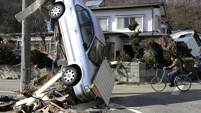 WIRE: A car leans against a wire from an electric pole in Miyako, northeastern Japan, Saturday, March 12, 2011, one day after an 8.9-magnitude quake and the tsunami it spawned hit the country's northeastern coast. (AP Photo/Kyodo News) MANDATORY CREDIT, NO LICENSING ALLOWED IN CHINA, HONG KONG, JAPAN, SOUTH KOREA AND FRANCE