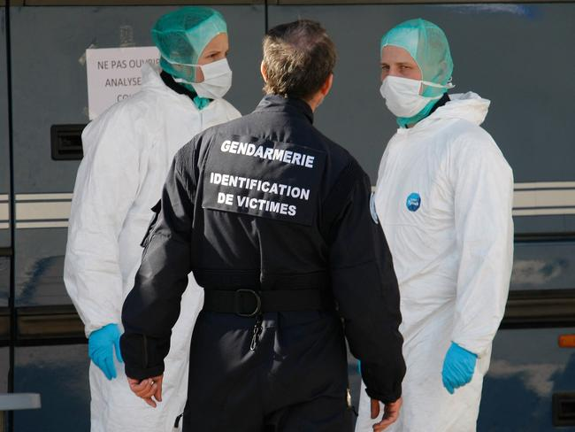 Criminology ... forensic experts work near a mobile investigation unit in Seyne-les-Alpes, France. Picture: Claude Paris