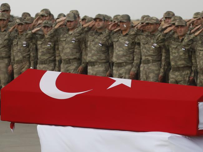 Turkish soldiers salute the Turkish flag-draped coffin of soldier Sefa Findik, killed in action in Syria on Sunday. Picture: AP
