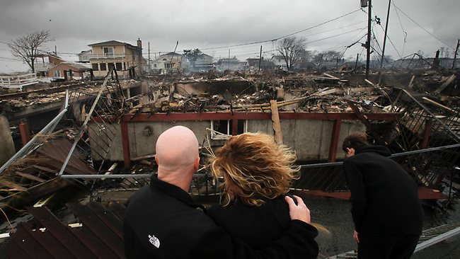 Robert Connolly, left, embraces his wife Laura as they survey the remains of the home owned by her parents that burned to the ground in the Breezy Point section of New York. Picture: AP/Mark Lennihan