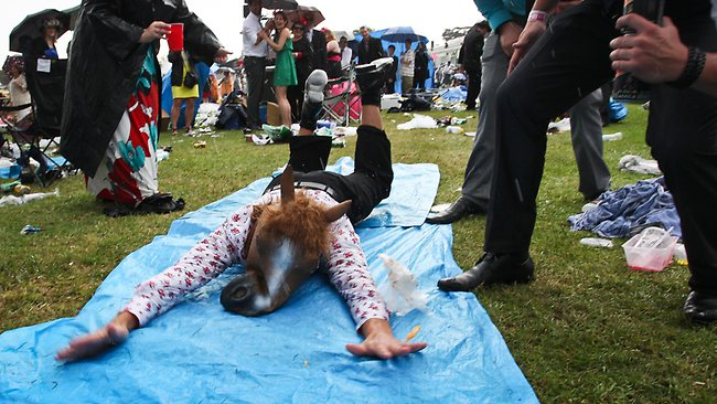 Racegoers make the most of wet conditions by setting up a slip n' slide