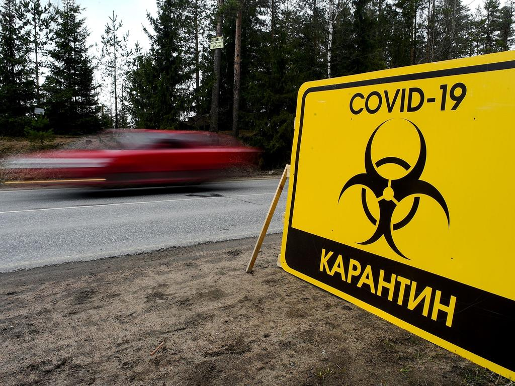"""A sign reading """"Quarantine COVID-19"""" is pictured at the entrance to the village of Pervomaiskoye outside Saint Petersburg. Coronavirus cases in Russia have skyrocketed. Picture: AFP"""