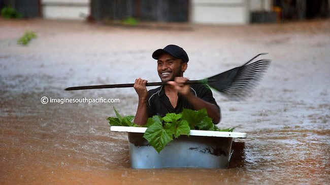 A resident of Fiji makes the most of a bathtub, paddling through the devastating floods. Picture: imaginesouthpacific.com.au