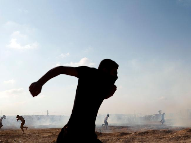 Palestinians run to take cover as an Israeli drone fires tear gas grenades in East Gaza City on Monday. Picture: AFP/Thomas Coex