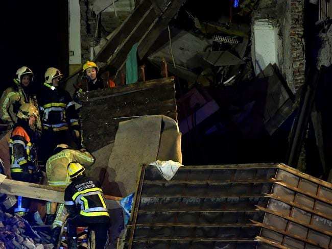 Firefighters inspect a collapsed building following the explosion. Picture: AFP