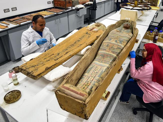 Restorers work on a sarcophagus part of the Tutankhamun collection at the restoration lab of the newly-built Grand Egyptian Museum (GEM) in Giza. Picture: AFP