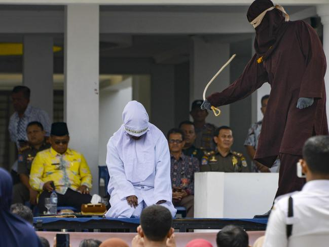 A woman is whipped in public by a member of the sharia police in Banda Aceh, Indonesia, on September 19. Picture: Chaideer Mahyuddin