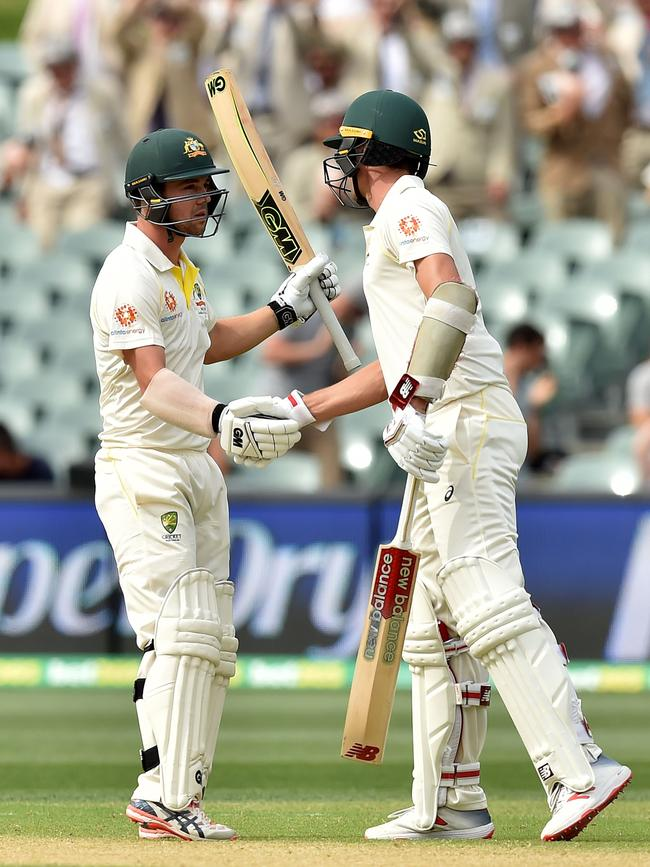 Hometown hero Travis Head is congratulated by Pat Cummins on reaching his 50 on Friday. Australia struggled to reach India's first innings score. Photo by PETER PARKS / AFP