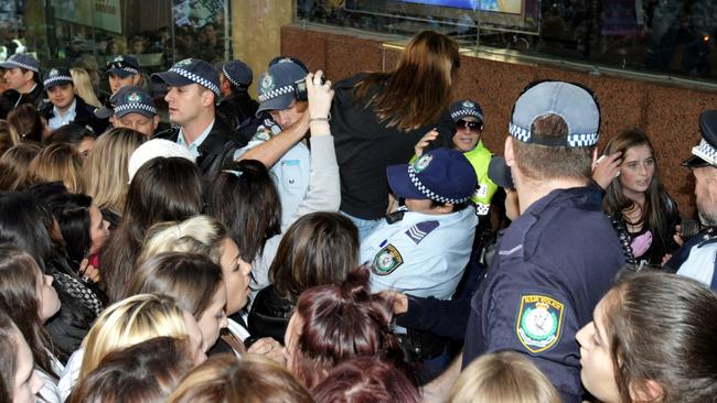 Crazed fans ... Police help girls out of the crush of fans as they look on as singer Justin Bieber performs at the Martin Place studios.
