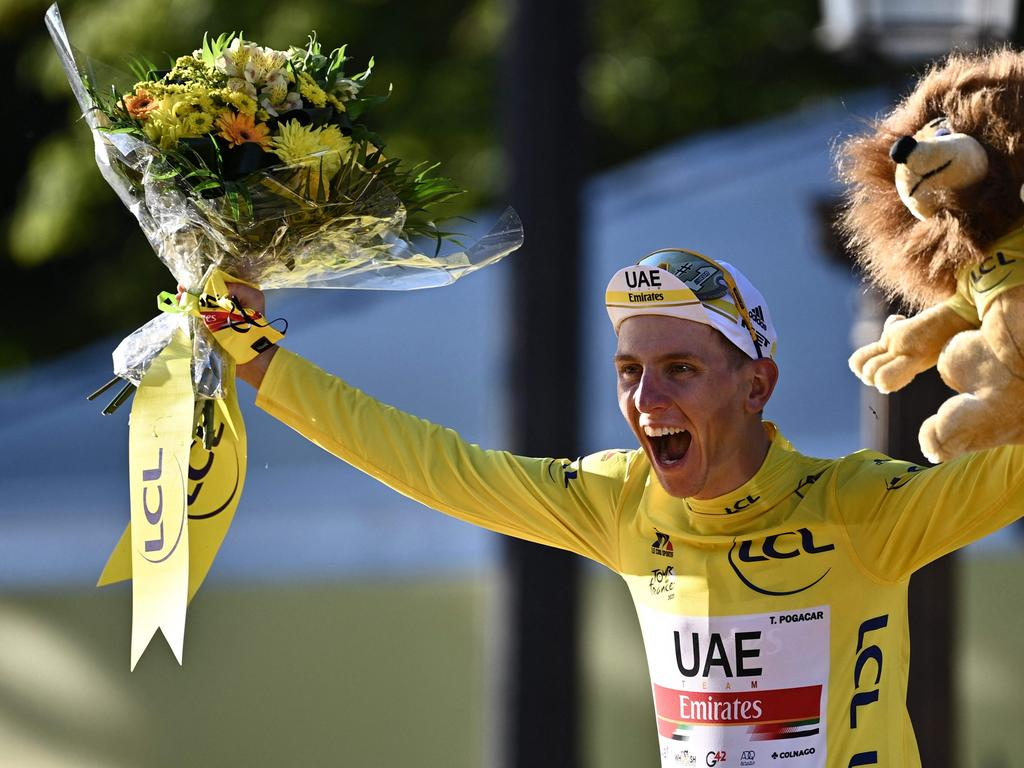 Winner Team UAE Emirates' Tadej Pogacar of Slovenia celebrates his overall leader yellow jersey on the podium at the end of the 21th and last stage of the 108th edition of the Tour de France cycling race, 108 km between Chatou and Paris Champs-Elysees, on July 18, 2021. (Photo by Anne-Christine POUJOULAT / AFP)