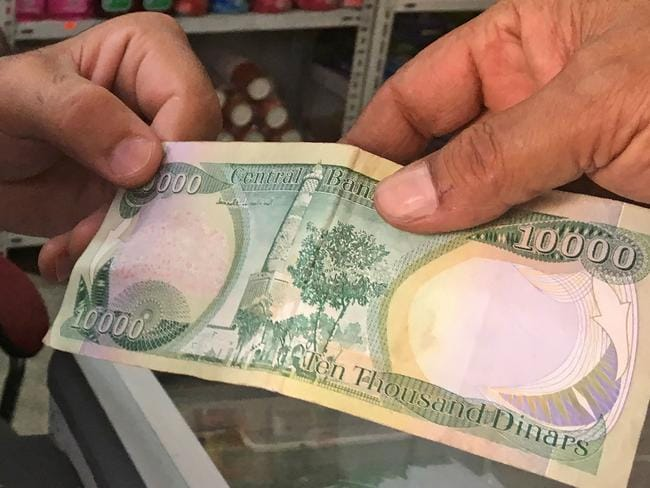 A 10,000-Iraqi dinar banknote bearing an image of the leaning minaret. Picture: Ali Choukeir/AFP