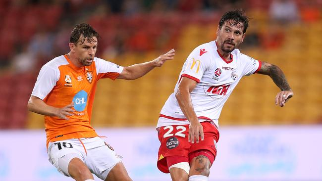 Brett Holman of the Brisbane Roar and Ersan Gulum of Adelaide United contest the ball