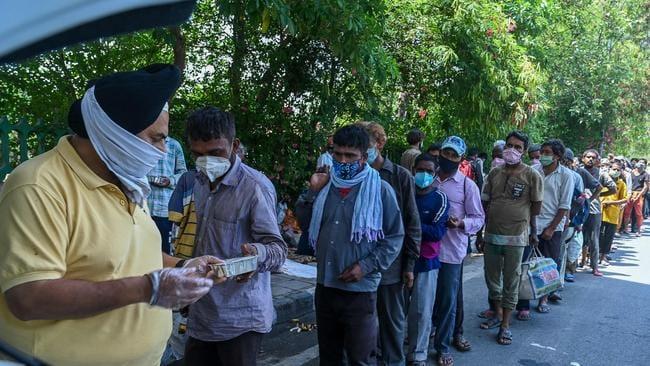 Men queue to work for food as volunteers in New Delhi during lockdown joblessness. Picture: Prakash Singh/AFP