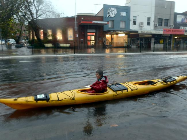 A woman paddles her kayak along Pittwater Road in Narrabeen as the floods continue to threaten homes. Picture: Jeremy Piper
