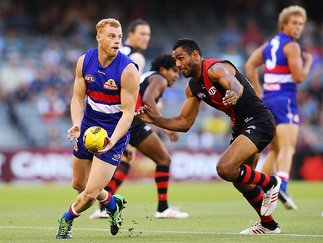MELBOURNE, AUSTRALIA - FEBRUARY 15: Adam Cooney of the Western Bulldogs runs with the ball away from Andrew Lovett-Murray during the round one AFL NAB Cup match between the Essendon Bombers and the Western Bulldogs at Etihad Stadium on February 15, 2013 in Melbourne, Australia. (Photo by Michael Dodge/Getty Images)