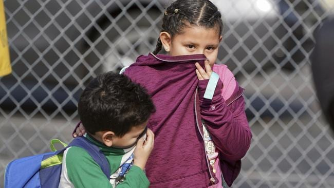 Children covering their noses and mouths leave school where multiple people were treated for jet fuel exposure at Park Avenue Elementary School. Picture: Scott Varley/The Orange County Register via AP.