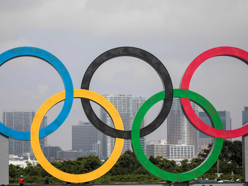 """(FILES) In this file photo a large size Olympic rings symbol is seen at """"Tokyo Waterfront"""" in the waters of Odaiba Marine Park on August 6, 2020, while being transferred back to the factory where it was manufactured for a safety inspection and to receive maintenance. - US President Joe Biden said late February 7, 2021 it remains to be seen if the US will send a team to the pandemic-postponed Tokyo 2020 Olympics, in a radio interview in which he also weighed in on diversity in sport. Japan's government, organisers and Olympic officials all insist the Games will go ahead this summer, and that extensive virus countermeasures will ensure the event is safe. Asked in a Super Bowl half-time radio interview with network Westwood One if he thought the Games would go ahead, Biden said any decision """"has to be based on science"""". (Photo by Behrouz MEHRI / AFP)"""