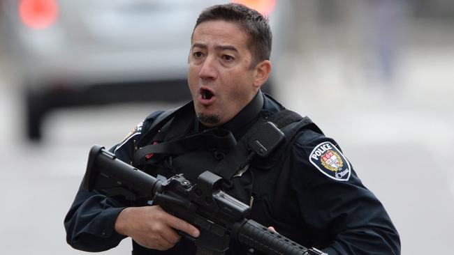 Alert ... an Ottawa police officer runs with his weapon drawn outside Parliament Hill. Picture: AP