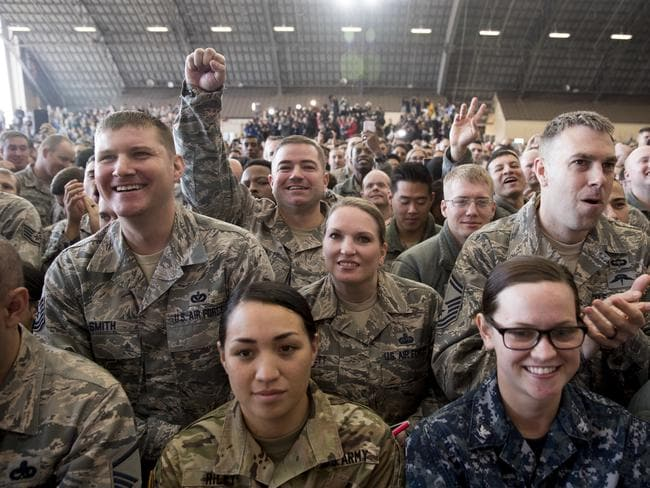 Members of the audience watch as President Donald Trump speaks at a hanger rally at Yokota Air Base. Picture: Andrew Harnick/AP
