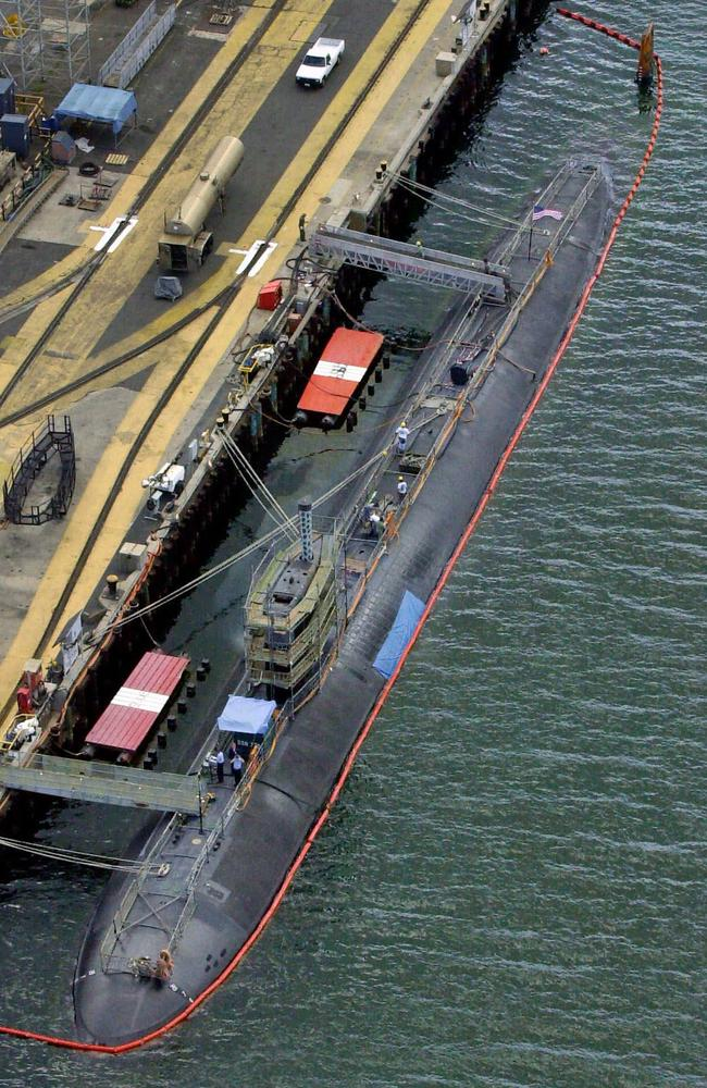 In this 2001 file photo, a blue tarp covers the damaged area of the USS Greeneville docked at Pearl Harbor as it undergoes repairs. The submarine's rudder and port side were damaged after it collided with a Japanese fishing vessel. China now says it wants to ban submarines operating underwater in the south and east China seas. Picture: AP