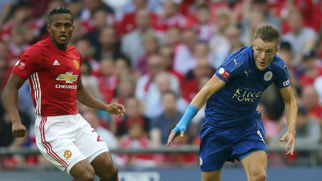 Leicester City's Jamie Vardy, centre, breaks from Manchester United's Luis Antonio Valencia, left.