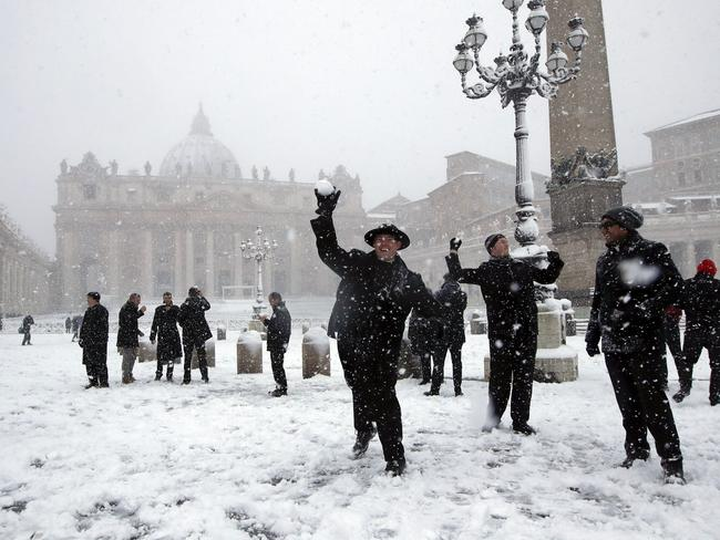 Shawn Rose, centre, throws a snowball in St. Peter's Square at the Vatican. Picture: AP