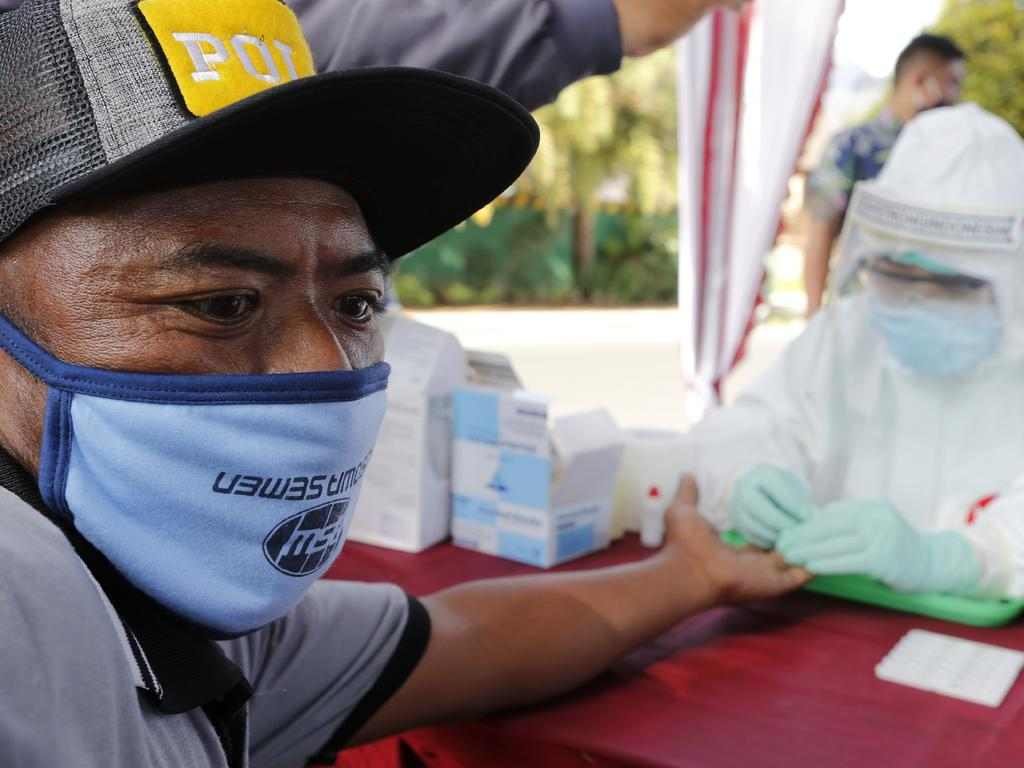 A health worker collects a man's blood sample for the coronavirus antibody test in Bali, Indonesia. Picture: AP