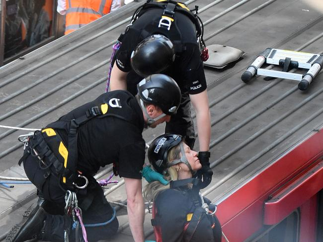 Police remove a climate change protester from the roof of a DLR train at Canary Wharf station. Picture: AFP