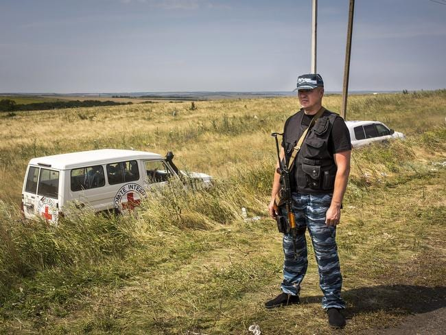 Rebels ... a member of a local militia stands guard as vehicles transporting observers from the Organisation for Security and Co-operation in Europe (OSCE) and International Committee of the Red Cross on a visit to the main crash site of Malaysia Airlines flight MH17. Picture: Getty