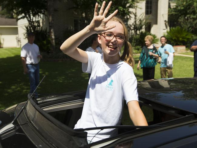 Surprise appearance ... Cassidy Stay, the lone survivor of a family massacre in Texas, waves to supporters during a community memorial at Lemm Elementary School.