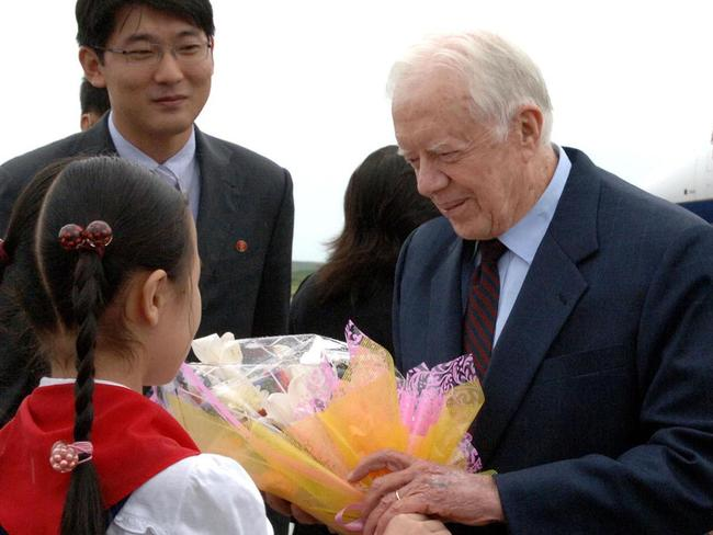 Former US president Jimmy Carter receives a bouquet of flowers from a girl upon arrival at Pyongyang airport during a 2010 mission to win the release of an American serving eight years of hard labour in the communist state. Picture: AFP/KCNA/KNS