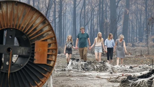 Mark and Cate Tregellas inspect their scorched property with daughters Jessica, Emily and Sarah. Picture: David Caird
