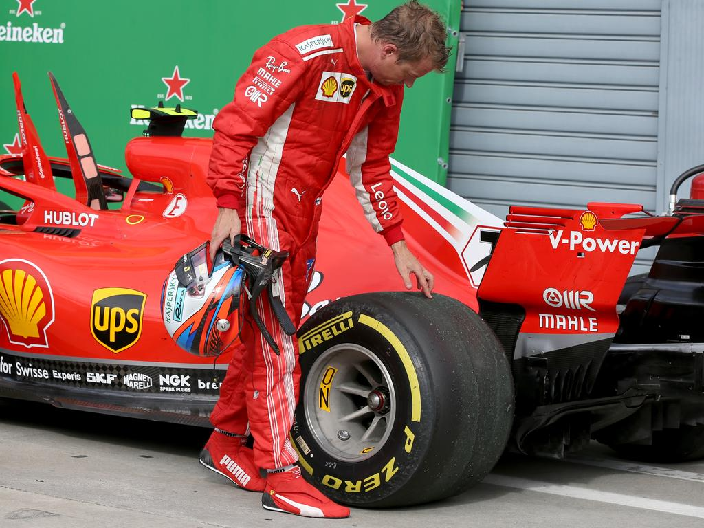 Raikkonen inspects his left rear tyre after the race, blistering causing it to lose a large patch of the tread.
