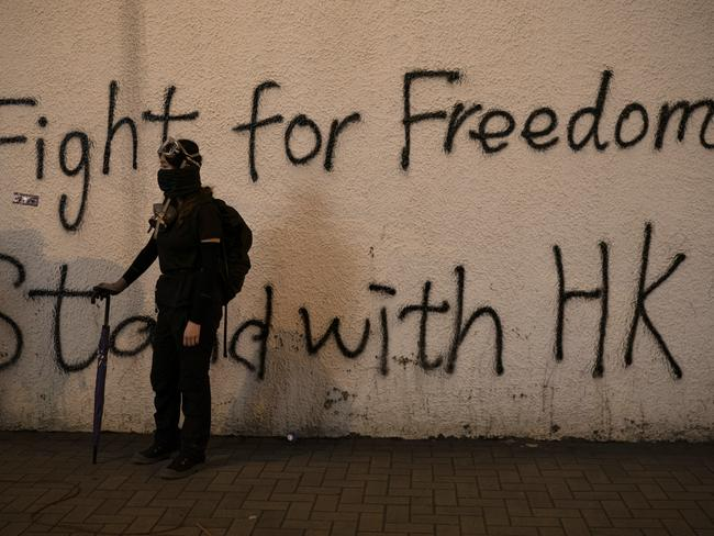 A black-clad protester stands by graffiti on the wall in Hong Kong. Picture: AP