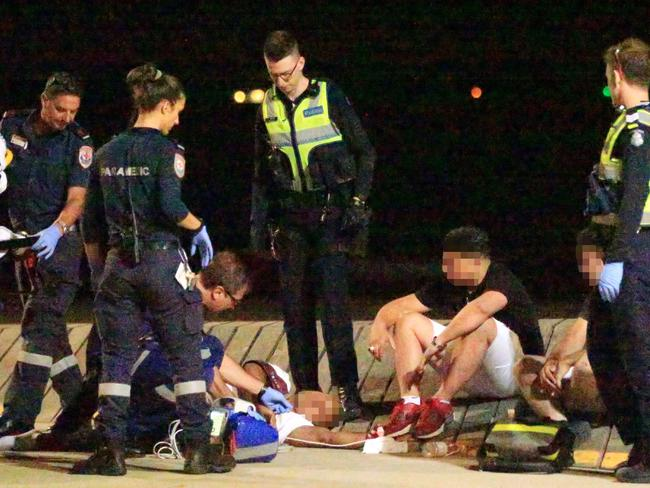 A victim of a gang of youths being assisted by paramedics on the St Kilda foreshore. Picture: Mark Stewart