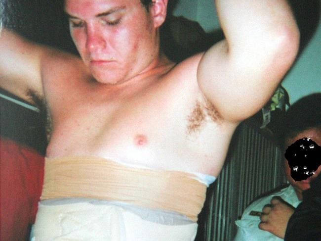 Scott Rush with heroin strapped to his body being searched at Denpasar Airport.