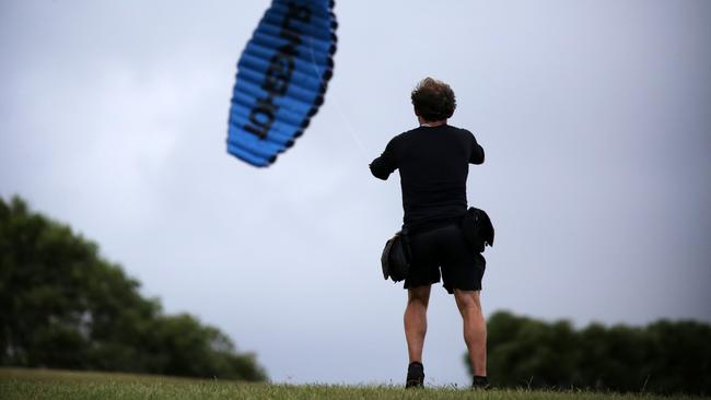 A man with his kite in strong winds at Sydney Park in Alexandria. Picture: Christian Gilles