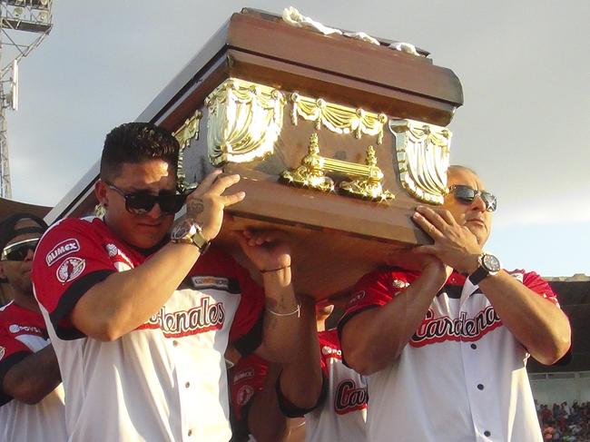 Players from the Cardenales de Lara baseball team carry their teammates' caskets.
