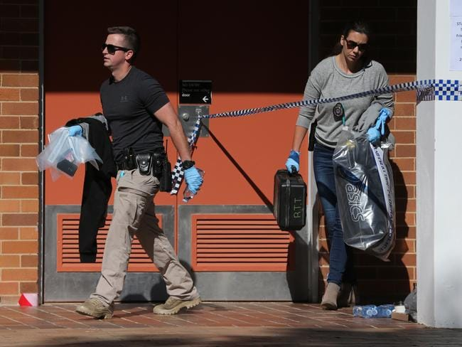 Police leave the Copeland GO32 classroom at ANU Canberra with evidence. Picture: Ray Strange.