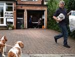 The owner of a house whose garage is being used as a polling station takes out his rubbish in Croydon, south of London on June 23, 2016. Millions of Britons began voting today in a bitterly-fought, knife-edge referendum that could tear up the island nation's EU membership and spark the greatest emergency of the bloc's 60-year history. / AFP PHOTO / BEN STANSALL