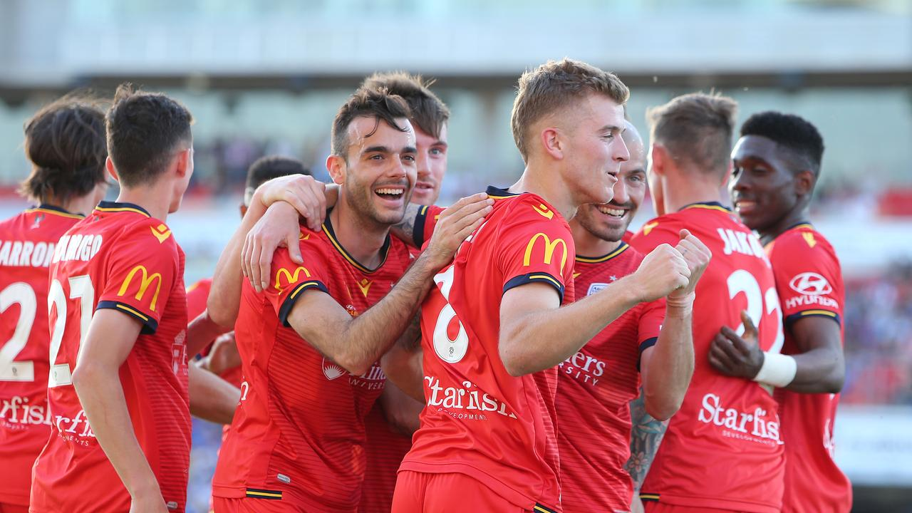 Adelaide celebrate Riley McGree's brilliant second goal against Newcastle. (Photo by Tony Feder/Getty Images)
