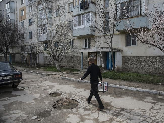 Game changer ... referendum staff walk on a street as they collect the votes in a predominantly Russian area of Bachchisaray, Ukraine. Picture: Dan Kitwood