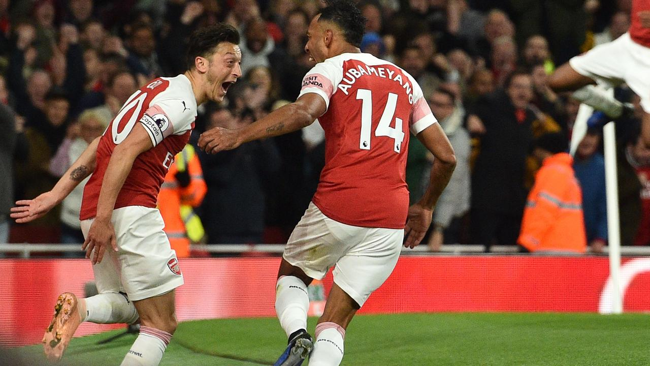 Pierre-Emerick Aubameyang (2nd L) celebrates with Mesut Ozil (L). (Photo by Glyn KIRK / IKIMAGES / AFP)
