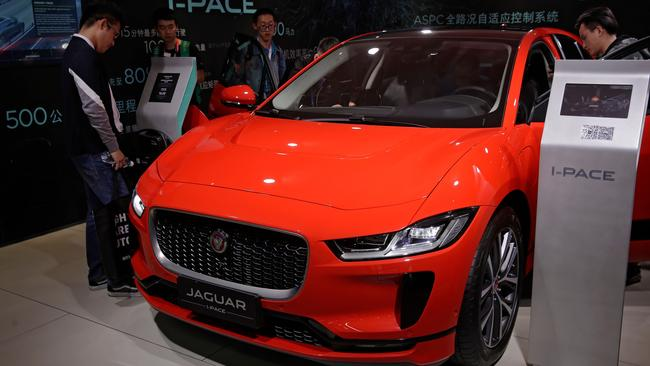 Journalists and visitors look at the Jaguar electric-powered I-Pace model. Picture: AP