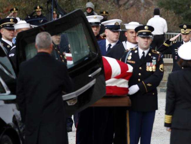 The flag-draped casket of the former president is carried by a joint services military honour guard from the hearse into the State Funeral . Picture: AP Photo/Alex Brandon, Pool