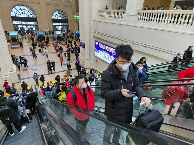 People wearing face masks ride escalators inside Hankou Railway Station. Picture: Getty Images