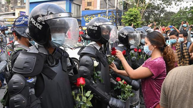A protester gives bouquets of flowers to a line of riot police during a demonstration against the military coup in Yangon on February 6, 2021. (Photo by STR / AFP)