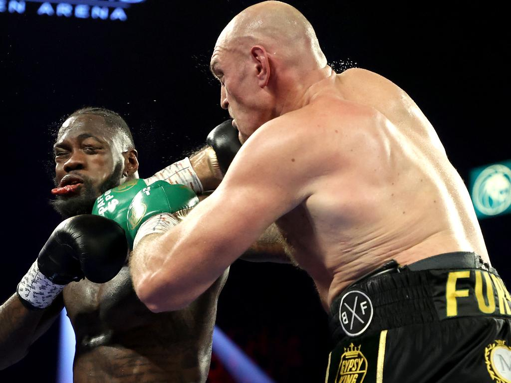 Tyson Fury lands a punch on Deontay Wilder's jaw.