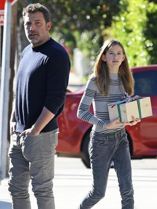 Violet, alongside her famous dad, takes a present into church. Picture: Vasquez/Backgrid