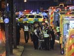 Police officers and members of the emergency services attend to a person injured in an apparent terror attack on London Bridge. Picture: AFP